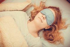 Sleeping woman wearing blindfold sleep mask. Tired woman sleeping in bed wearing blindfold sleep mask. Young girl taking nap Royalty Free Stock Photos