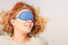 Sleeping woman wearing blindfold sleep mask. Tired woman sleeping in bed wearing blindfold sleep mask. Young girl taking nap Stock Images