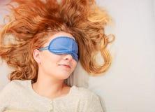 Sleeping woman wearing blindfold sleep mask. Tired woman sleeping in bed wearing blindfold sleep mask. Young girl taking nap Royalty Free Stock Images