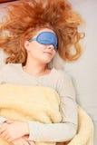 Sleeping woman wearing blindfold sleep mask. Tired woman sleeping in bed wearing blindfold sleep mask. Young girl taking nap Royalty Free Stock Image