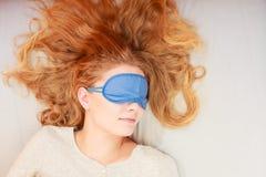 Sleeping woman wearing blindfold sleep mask. Tired woman sleeping in bed wearing blindfold sleep mask. Young girl taking nap Stock Photography