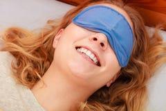Sleeping woman wearing blindfold sleep mask. Tired woman sleeping in bed wearing blindfold sleep mask. Young girl taking nap Stock Photo