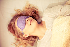 Sleeping woman wearing blindfold sleep mask. Tired woman sleeping in bed wearing blindfold sleep mask. Young girl taking nap. Instagram filtered Royalty Free Stock Photos