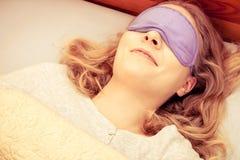 Sleeping woman wearing blindfold sleep mask. Tired woman sleeping in bed wearing blindfold sleep mask. Young girl taking nap. Instagram filtered Stock Image