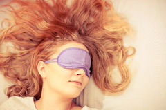 Sleeping woman wearing blindfold sleep mask. Tired woman sleeping in bed wearing blindfold sleep mask. Young girl taking nap. Instagram filtered Stock Photography