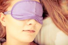 Sleeping woman wearing blindfold sleep mask. Tired woman sleeping in bed wearing blindfold sleep mask. Young girl taking nap. Instagram filtered Royalty Free Stock Photo