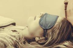Sleeping woman wearing blindfold sleep mask. Tired woman sleeping in bed wearing blindfold sleep mask. Young girl taking nap. Sepia Royalty Free Stock Photos