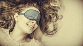 Sleeping woman wearing blindfold sleep mask. Tired woman sleeping in bed wearing blindfold sleep mask. Young girl taking nap. Sepia Stock Images