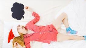 Sleeping woman wearing pajamas and Santa Claus hat Stock Image