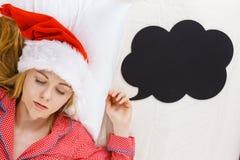 Sleeping woman wearing pajamas and Santa Claus hat Stock Photo