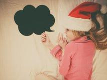 Sleeping woman wearing pajamas and Santa Claus hat Royalty Free Stock Photography