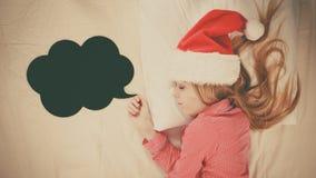 Sleeping woman wearing pajamas and Santa Claus hat Royalty Free Stock Photo
