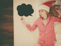 Sleeping woman wearing pajamas and Santa Claus hat. Sleeping woman waiting for Christmas season wearing pajamas and Santa Claus hat lying in bed dreaming about Stock Photo