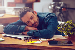 Sleeping at working place. Young man leaning his head on desk and keeping eyes closed while sitting at his working place stock photo