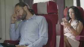Sleeping young corporate man commuter and woman using smartphone surfing on internet while commuting in train going to work -. Sleeping young corporate man stock footage