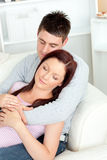 Sleeping young couple lying together on the sofa Stock Photos