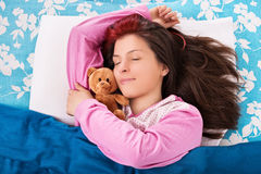 Sleeping young girl hugging her bear Royalty Free Stock Images