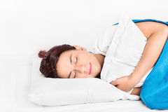 Sleeping. Young girl sleeping, hugging a pillow isolated on white background Stock Photography