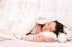 Sleeping young woman and alarm clock Royalty Free Stock Photo