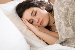Sleeping young woman. Young brunette woman sleeping in bed covered with a beige flowered quilt Stock Image