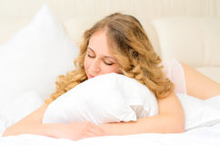 Sleeping young woman embracing pillow Stock Photography