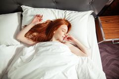 Sleeping young woman lies in bed with eyes closed. top view. Redhead sleeping young woman lies in bed with eyes closed. top view royalty free stock images