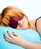 Sleeping Young Woman In Sleep Eye Mask. On blue furnishing Royalty Free Stock Images