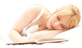 Sleeping young woman in white bedding Stock Photo