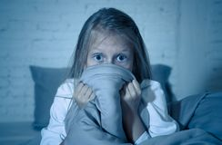 Sleepless cute girl in fear at night hiding behind the blanket afraid of dark and monsters stock photos