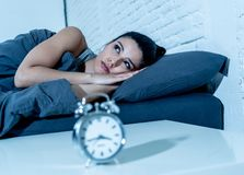 Attractive woman staring at alarm clock trying to sleep feeling stressed depressed and sleepless. Sleepless and desperate beautiful latin woman awake at night stock photos
