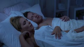 Sleepless female lying in bed near husband, having insomnia, family fight. Stock footage stock video