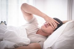Sleepless hangover man on bed up with headache royalty free stock photo