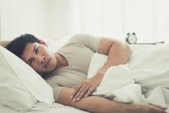 Sleepless man on bed woke up with headache royalty free stock image