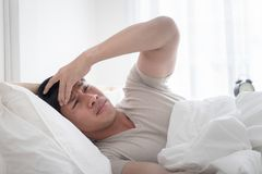 Sleepless man on bed woke up with headache stock images