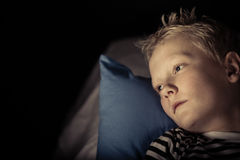 Sleepless little boy laying on pillow Royalty Free Stock Images