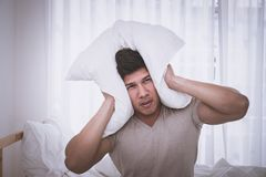 Sleepless male cover head fro noise and headache. Sleepless Asian male cover head fro noise and headache royalty free stock image