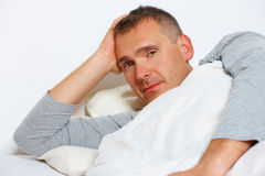 Sleepless man. Sleepless night. Man in bed suffering from insomnia royalty free stock images