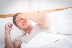 Sleepless man on bed woke up with headache stock photos