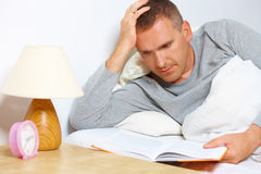 Sleepless man reading a book. On the bed stock photography