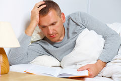 Sleepless man reading a book. On the bed stock photo