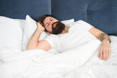 Sleepless night. Sleep disorders concept. Man bearded hipster having problems with sleep. Guy lying in bed try to relax. And fall asleep. Relaxation techniques stock image
