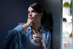 Sleepless woman having a glass of milk. Sleepless sad woman sitting on kitchen floor having a glass of milk stock photography