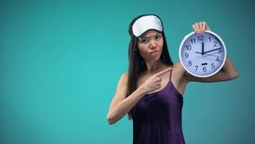 Sleepless woman in pajamas and with blindfall on face pointing at clock insomnia. Stock footage stock video