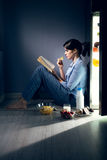 Sleepless woman reading in the kitchen Royalty Free Stock Photos