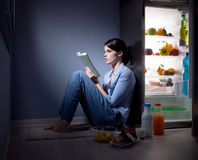 Sleepless woman reading in the kitchen. Sleepless woman sitting on the kitchen floor reading a book and eating royalty free stock photos