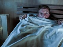 Sleepless young man lying in bed stressed and scared suffering nightmare and horror bad dream grabbing duvet frightened and parano. Id in sleeping disorder and Royalty Free Stock Photo