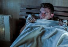 Sleepless young man lying in bed stressed and scared suffering nightmare and horror bad dream grabbing duvet frightened and parano. Id in sleeping disorder and Royalty Free Stock Images