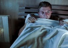 Sleepless young man lying in bed stressed and scared suffering nightmare and horror bad dream grabbing duvet frightened and parano. Id in sleeping disorder and Stock Photos