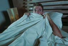 Sleepless young man lying in bed stressed and scared suffering nightmare and horror bad dream grabbing duvet frightened and parano. Id in sleeping disorder and Stock Photo