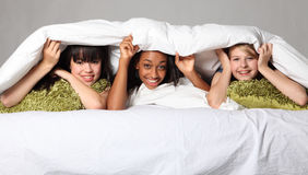 Sleepover party fun teenage girls laughing in bed Stock Image